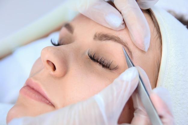 Mujer joven depilarse las cejas con pinzas de cerca.