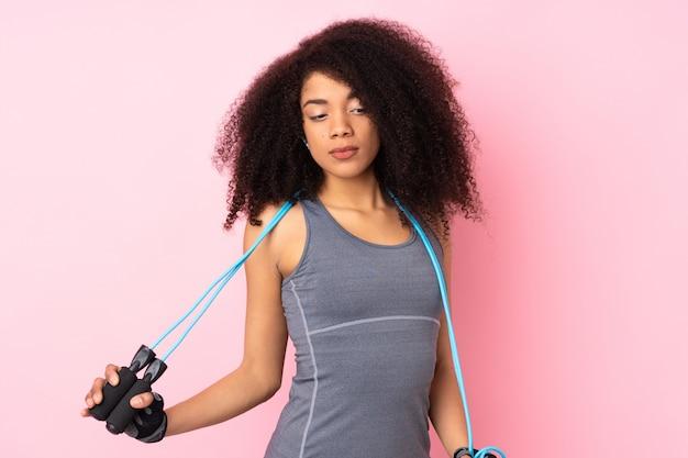 Mujer joven del deporte afroamericano en la pared rosada con saltar la cuerda