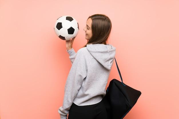 Mujer joven deporte aislado rosa sosteniendo un balón de fútbol