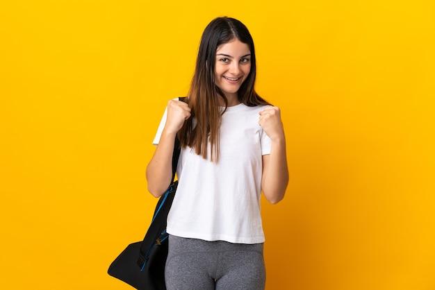 Mujer joven deporte con bolsa de deporte aislada en la pared amarilla celebrando una victoria en la posición ganadora