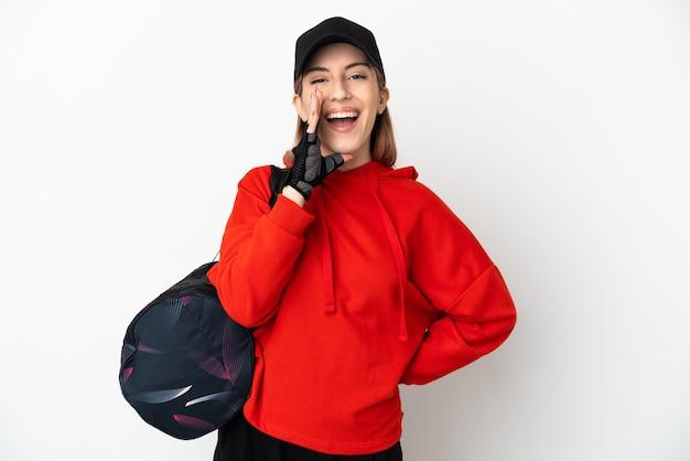 Mujer joven deporte con bolsa de deporte aislado en la pared blanca gritando con la boca abierta