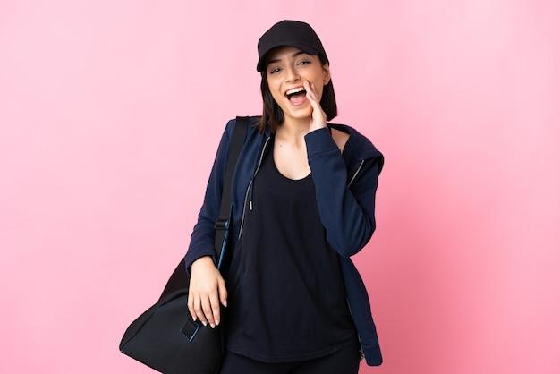Mujer joven deporte con bolsa de deporte aislado en la pared rosa gritando con la boca abierta
