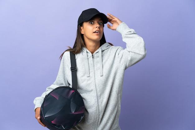 Mujer joven deporte con bolsa de deporte haciendo gesto de sorpresa mientras mira hacia el lado