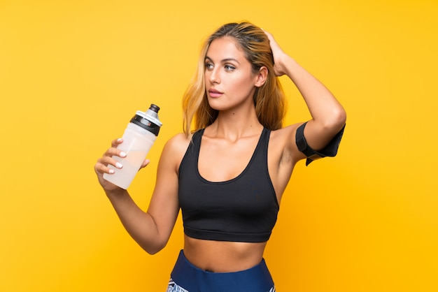 Mujer joven del deporte con una botella de agua sobre la pared aislada