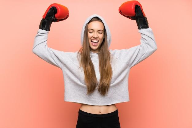 Mujer joven deporte feliz sobre rosa aislado con guantes de boxeo
