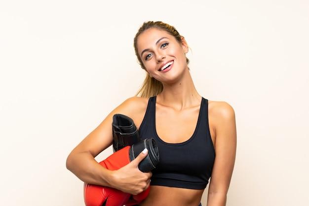 Mujer joven deporte con guantes de boxeo sobre pared aislada