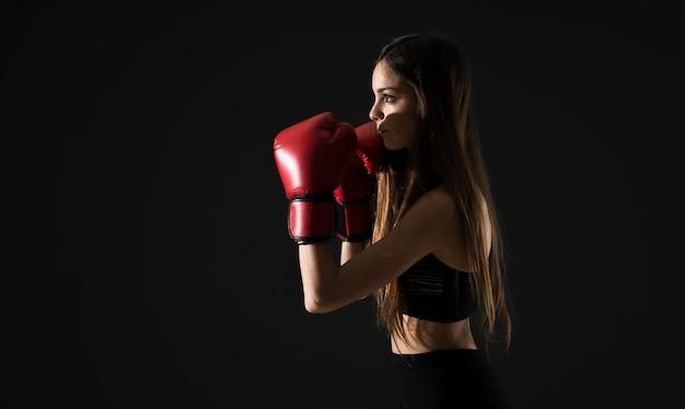Mujer joven del deporte con los guantes de boxeo