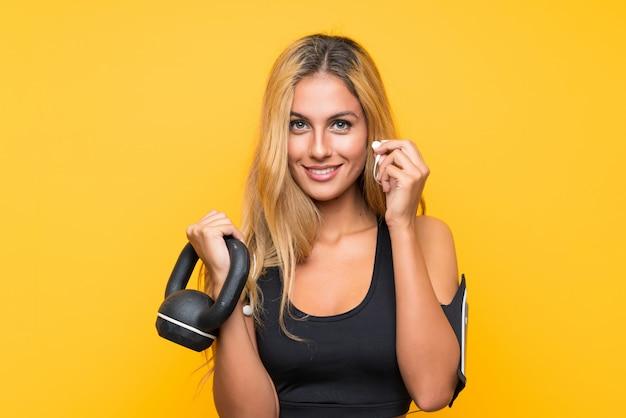 Mujer joven deporte haciendo pesas con pesas rusas