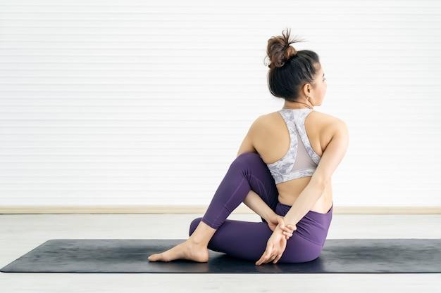 Mujer joven deporte haciendo yoga pose en mat en casa