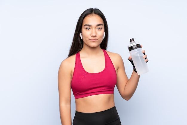 Mujer joven deporte indio en la pared azul con botella de agua deportiva