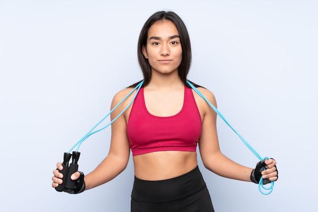 Mujer joven deporte indio en la pared azul con saltar la cuerda