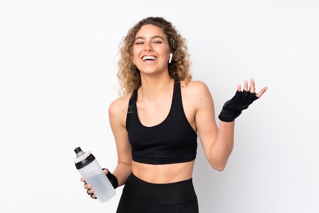 Mujer joven deporte en pared blanca con botella de agua deportiva