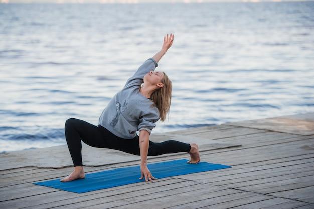Mujer joven deporte practicando yoga en la playa