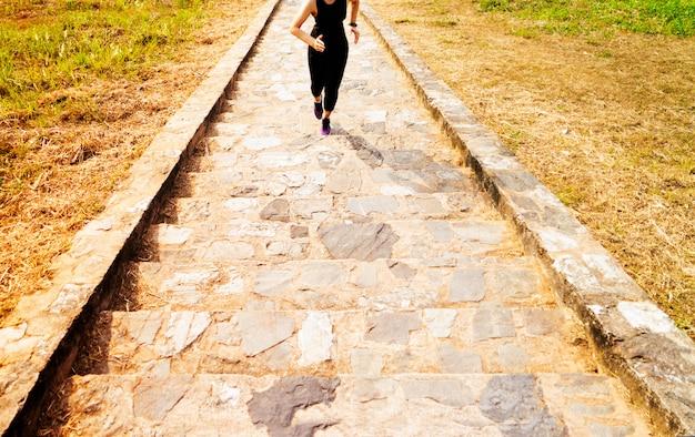 Mujer joven del deporte que corre al aire libre arriba en el cielo azul