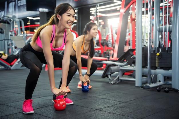 Mujer joven del deporte que se resuelve con la bola de la caldera en gimnasio