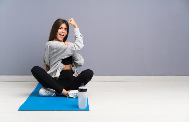 Mujer joven del deporte que se sienta en el piso con la estera que hace gesto fuerte