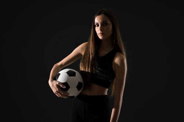 Mujer joven del deporte que sostiene un balón de fútbol