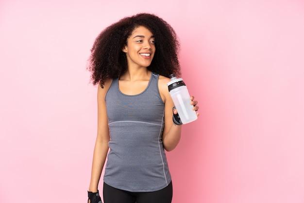 Mujer joven deporte en rosa con botella de agua deportiva