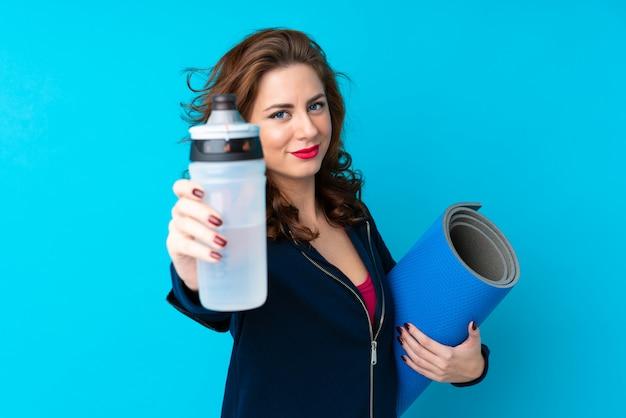 Mujer joven deporte sobre azul aislado con botella de agua deportiva y con una estera