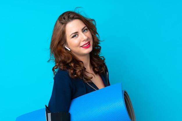 Mujer joven del deporte sobre fondo azul aislado con una estera y una sonrisa