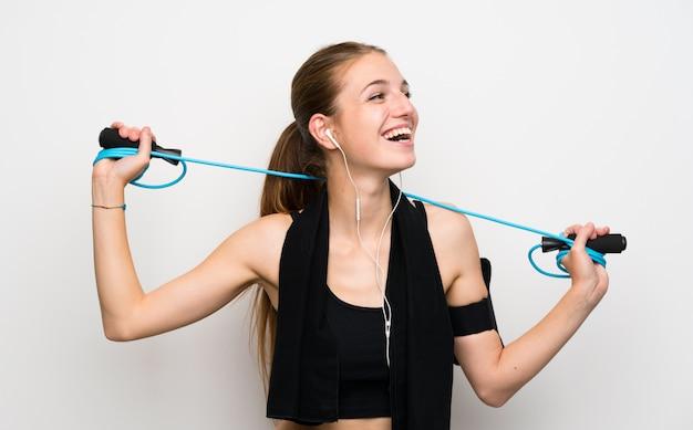 Mujer joven del deporte sobre fondo blanco aislado con la cuerda de salto