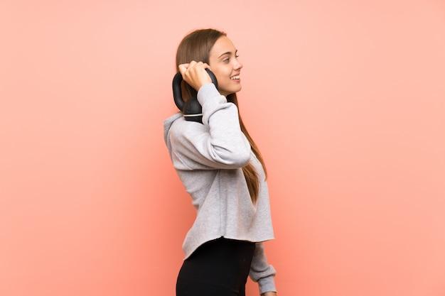 Mujer joven del deporte sobre fondo rosado aislado