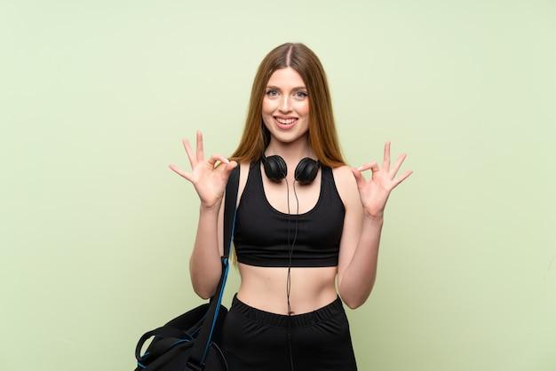 Mujer joven del deporte sobre el fondo verde aislado que muestra una muestra aceptable con los dedos