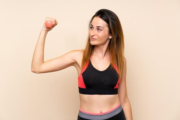 Mujer joven del deporte sobre la pared aislada que hace levantamiento de pesas