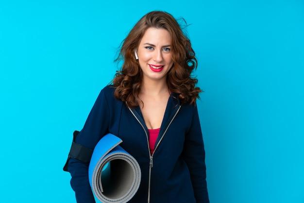 Mujer joven del deporte sobre la pared azul aislada