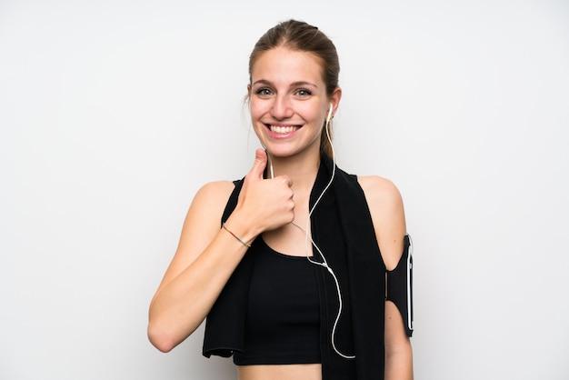 Mujer joven del deporte sobre la pared blanca aislada que da un gesto de los pulgares para arriba