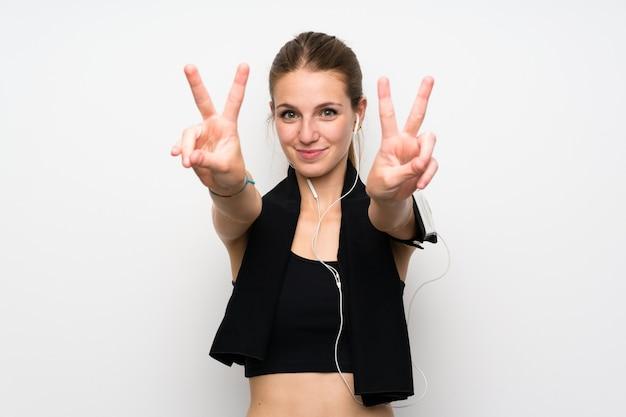 Mujer joven del deporte sobre la pared blanca aislada que sonríe y que muestra la muestra de la victoria
