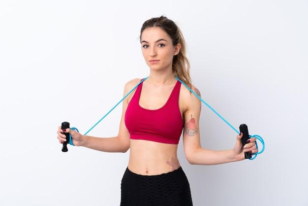 Mujer joven deporte sobre pared blanca aislada con saltar la cuerda