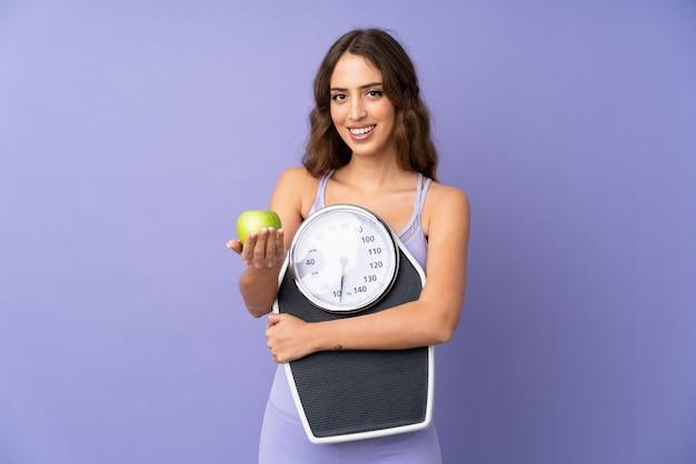 Mujer joven del deporte sobre la pared púrpura que sostiene la máquina de pesaje y que ofrece una manzana