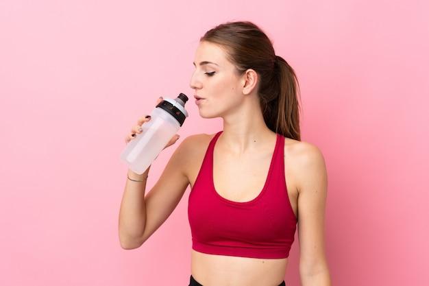 Mujer joven deporte sobre pared rosa aislado con botella de agua deportiva