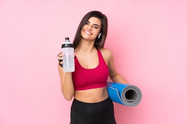 Mujer joven deporte sobre pared rosa con botella de agua deportiva y con una estera