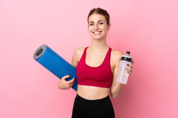 Mujer joven del deporte sobre la pared rosada aislada con la botella de agua deportiva y con una estera