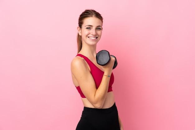 Mujer joven del deporte sobre la pared rosada aislada que hace levantamiento de pesas