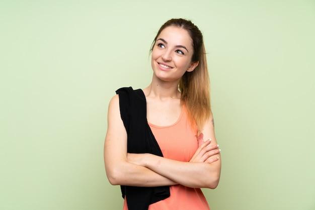 Mujer joven del deporte sobre la pared verde que mira para arriba mientras que sonríe
