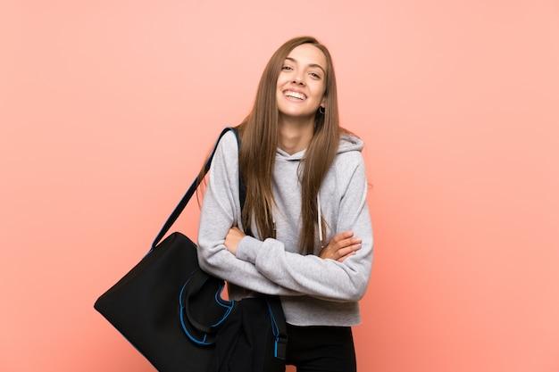 Mujer joven del deporte sobre la risa rosada aislada del fondo