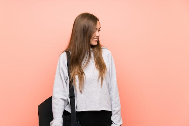Mujer joven del deporte sobre rosa aislado que mira al lado