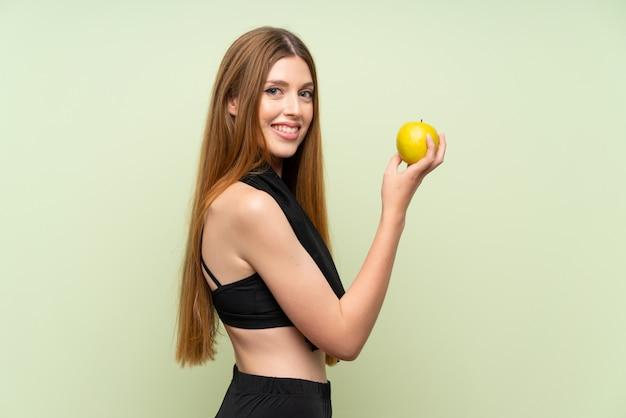 Mujer joven del deporte sobre verde aislado con una manzana