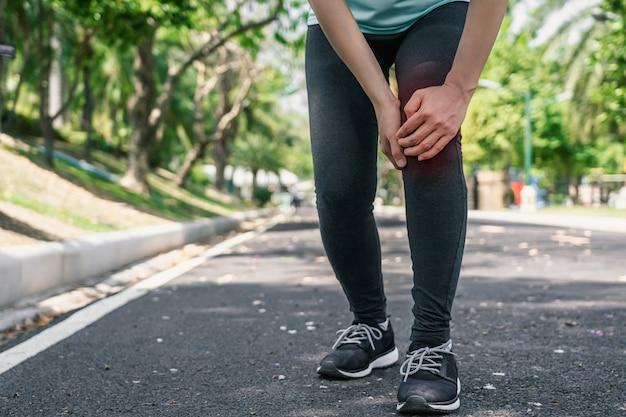 La mujer joven del deporte sostiene su rodilla herida adentro al aire libre.