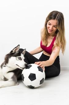 Mujer joven deporte con su perro sentado en el suelo
