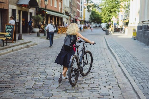 Mujer joven de los deportes en una bicicleta en una ciudad europea. el deporte en entornos urbanos.