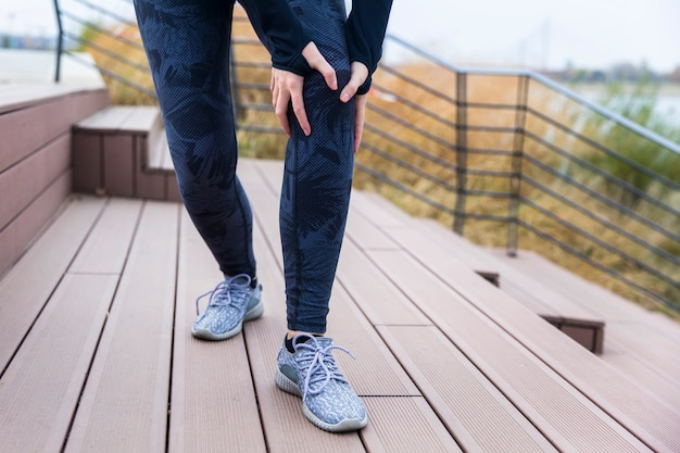 Mujer joven de los deportes que estira las piernas