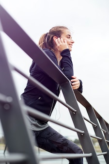 Mujer joven deportiva con los auriculares que se inclinan en la cerca y que miran lejos al aire libre