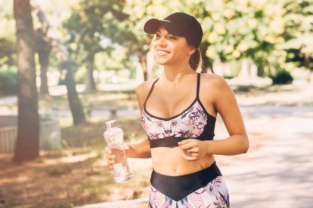 Mujer joven deportiva feliz que sostiene la botella de agua plástica