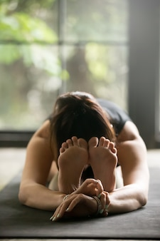 Mujer joven deportiva en pose de curva hacia adelante sentado
