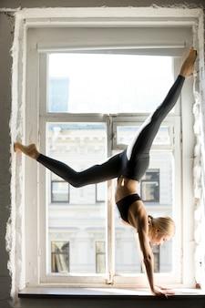 Mujer joven deportiva en la postura del árbol mirando hacia abajo, el alféizar de la ventana