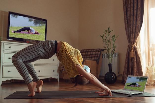 Mujer joven deportiva que toma lecciones de yoga en línea y practica en casa mientras está en cuarentena. concepto de estilo de vida saludable, bienestar, estar seguro durante la pandemia de coronavirus, en busca de un nuevo pasatiempo.